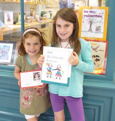Two young authors showing off their published books